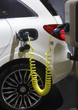 Charging electric car. Closeup of white hybrid electric car while batteries are being charged at a refueling point Stock Images