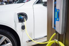 Charging an electric car with the power cable supply royalty free stock photography