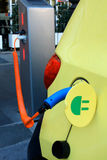 Charging an electric car with the power cable supply plugged in. Stock Images