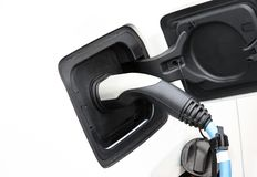 Charging an electric car. Recharging of an an electric car with a plug and cable royalty free stock photo