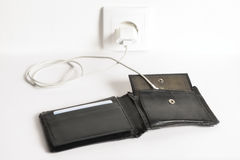 Charging an Empty Wallet. Funny concept of charging an empty wallet on a power socket Royalty Free Stock Photo