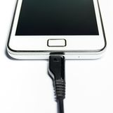 Charging the mobile phone isolated Stock Image