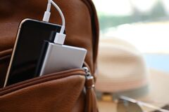 Charging mobile phone with power bank in backpack, closeup. Space for text