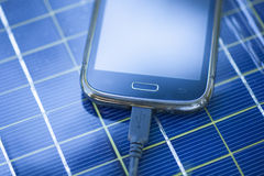 Charging mobile phone with solar charger Royalty Free Stock Images
