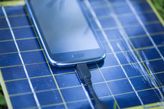 Charging mobile phone with solar charger Royalty Free Stock Photos