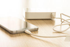 Charging mobile smartphones. Mobile smart phones charging with energy bank on wooden desk Stock Images