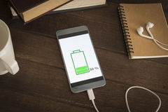 Charging mobile smartphones. Mobile smart phones charging on wooden desk Royalty Free Stock Photography
