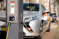 Charging silver electric car . Charging modern silver electric car in public charging station Royalty Free Stock Photography