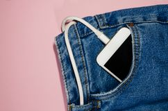 Charging phone in jeans royalty free stock image