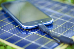Charging smart-phone with solar charger Stock Image