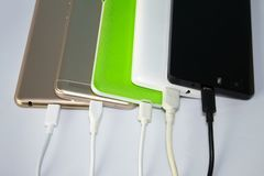 Charging smart phones on white background. A lot of charging phones with usb cables stock images