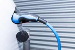 Charging Tesla car in the home garage. As eco and economical mobility concept Stock Images