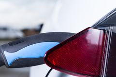 Charging Tesla electric car. Outdoors. Green fuel and hybrid energy concept Royalty Free Stock Image