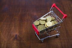 Chariot à achats avec des pièces de monnaie sur une table en bois Images libres de droits