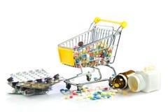 Chariot à achats avec des pilules d'isolement sur la pharmacie blanche de fond Photos stock