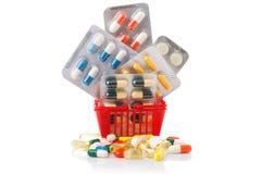 Chariot à achats avec des pilules et médecine d'isolement sur le blanc Photographie stock