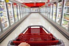 Chariot à achats de tache floue de mouvement dans le supermarché Photo stock