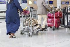 Chariot à bagage d'aéroport avec des valises, femme non identifiée d'homme marchant dans l'aéroport, station, France Photos stock