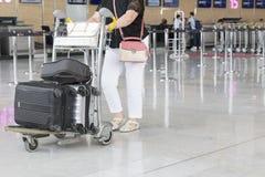 Chariot à bagage d'aéroport avec des valises, femme non identifiée d'homme marchant dans l'aéroport, station, France Photographie stock libre de droits