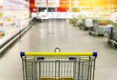 Chariot à l'épicerie Soustrayez la photo brouillée du magasin avec le chariot à l'arrière-plan de bokeh de magasin Images stock