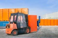 Chariot élévateur déchargeant la remorque de camion semi avec les boîtes en carton enveloppées dehors l'entrepôt en plein air fon images libres de droits