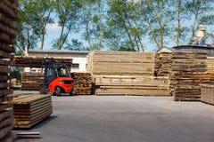 Chariot élévateur fonctionnant dans l'industrie de bois de charpente images stock