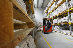 Chariot élévateur fonctionnant dans un entrepôt en bois Image stock