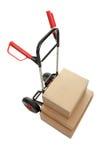 Chariot avec des boîtes en carton sur le fond blanc Photos stock