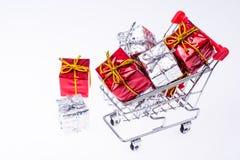 Chariot avec des cadeaux de Noël sur le fond blanc Photos stock
