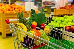 Chariot avec des fruits frais et des légumes au centre commercial photos stock