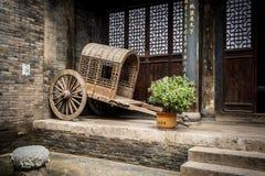 Chariot chinois antique vide se reposant contre un mur de briques images stock
