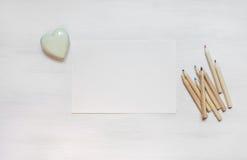 Chariot d'invitation avec le coeur et pensils sur le backgroun en bois blanc Images libres de droits