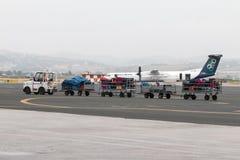 chariot de bagage sur la piste de l'aéroport Macédoine par jour pluvieux Photos libres de droits