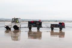 chariot de bagage sur la piste de l'aéroport Macédoine par jour pluvieux Photo libre de droits