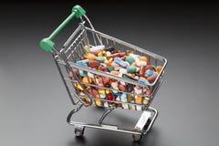 Chariot de boutique avec différentes pilules colorées sur le noir Photo stock