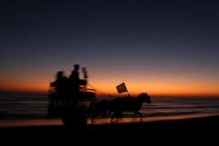 Chariot de cheval fonctionnant dans le coucher du soleil Photographie stock