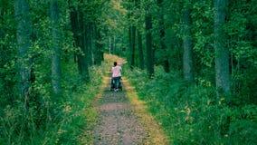 Chariot de mère et de bébé entrant dans les bois Images stock