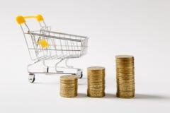 Chariot de poussée d'épicerie de supermarché pour faire des emplettes avec la poignée en plastique jaune à côté des piles de pièc image stock