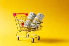 Chariot de poussée d'épicerie de supermarché pour faire des emplettes avec les éléments roses sur la poignée avec des paquets d'a photos libres de droits