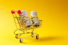 Chariot de poussée d'épicerie de supermarché pour faire des emplettes avec les éléments roses sur la poignée avec des paquets d'a images libres de droits