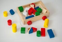 Chariot en bois à enfants avec les cubes en bois colorés, cylindres Photographie stock