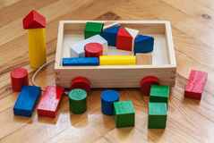 Chariot en bois à enfants avec les cubes en bois colorés, cylindres Photos libres de droits