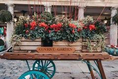 Chariot en bois avec des décorations de Noël de fleurs dans Covent Garden photos stock