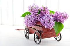 Chariot en bois décoratif complètement des lilas Images stock