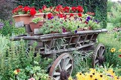 Chariot en bois rempli de fleurs dans des pots en parc photographie stock