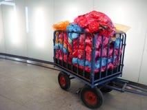 Chariot en métal pour la collecte des déchets avec une grande pile des sachets en plastique colorés remplis de déchets assortis p photos stock