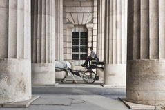 Chariot hippomobile passant par le collonnade Images libres de droits