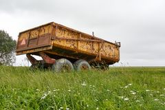 Chariot jaune rouillé de tracteur de ferme dans le paysage vert Image libre de droits