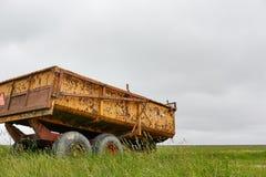 Chariot jaune rouillé de tracteur de ferme dans le paysage vert Photographie stock