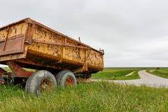 Chariot jaune rouillé de tracteur de ferme dans le paysage vert Photo stock